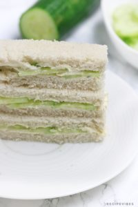 the sandwiches on a plate with cucumber in the background.