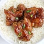 honey garlic chicken served on rice and garnished with spring onions.