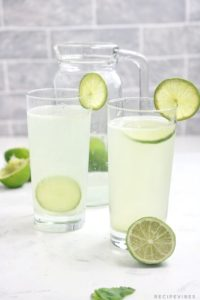 lime juice in 2 glass cups and a pitcher.