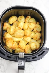 cooked dish in air fryer basket.