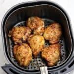 air fried chicken thighs in fryer basket.