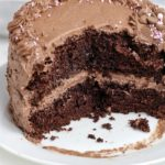 frosted round chocolate cake with a portion cut out.
