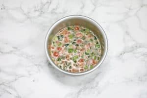 omelette egg mixture in a round baking pan.