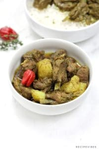 curry goat served in a white plate and garnished with whole scotchbonnet.