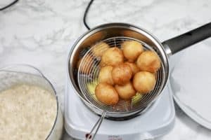 cooked puff puff scooped out of oil.
