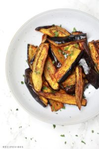 Air fryer eggplant fries served on a plate and garnished with parsley.